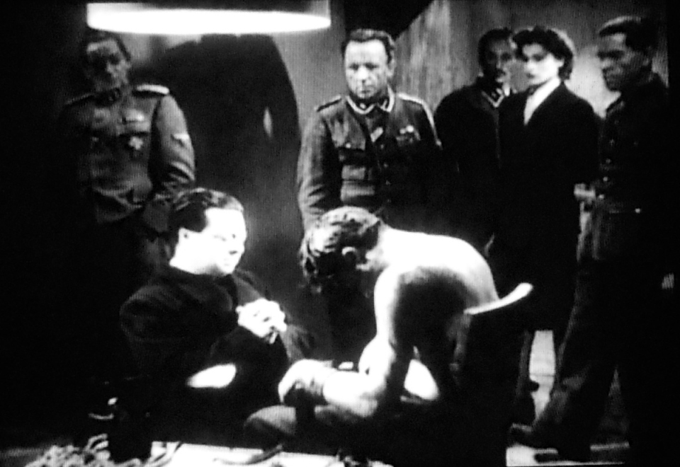 The priest, Don Pietro, kneels at the foot of the dead Communist, Girgio Manfredi